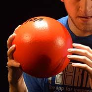 A young man holds up a dogeball ready to throw